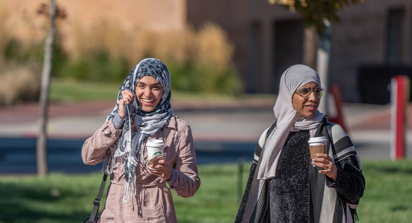 two women with head scarves walking on campus